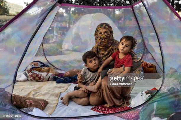 Farzia who lost her husband in Baghlan one week ago to fighting by the Taliban sits with her children, Subhan and Ismael in a tent at a makeshift IDP...