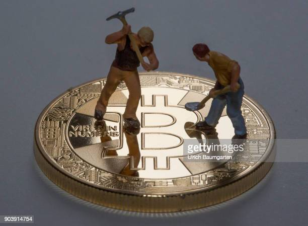 Fascination and uncertainty Bitcoin Symbol photo on the topic crypto currency Bitcoin The picture shows Bitcoin and workers with a pickaxe and a...