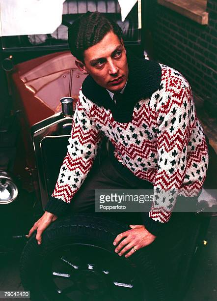 Fashion 1960's A young man wearing a boldly patterned sweater changes a wheel on his vintage car