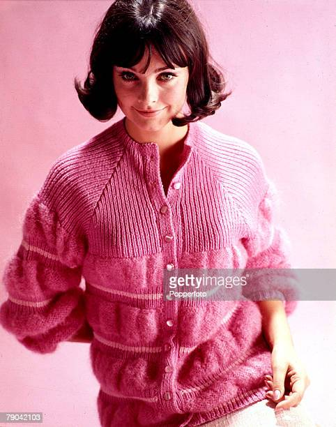 Fashion 1960's A young woman wearing a high neck pink cardigan that has a ribbed yoke with gathered and puffed bands around the lower half