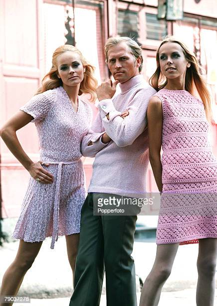 Fashion 1960s Knitwear A man stands between two young women on a street wearing coordinating pink knitwear The man has a pale pink polo neck sweater...