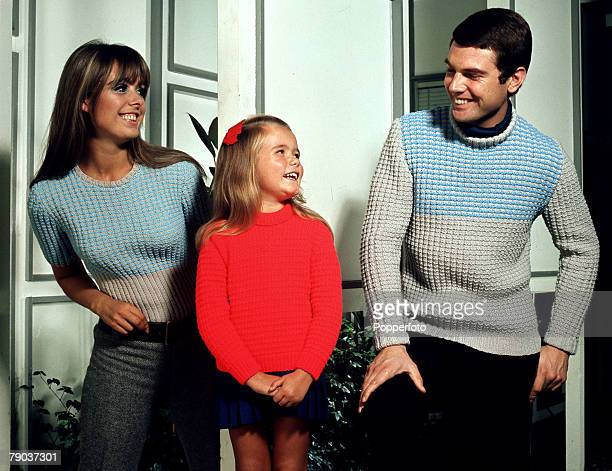 Fashion 1960s Knitwear A young couple wearing coordinating grey and blue sweaters stand with a young girl who is wearing a contrasting bright red...