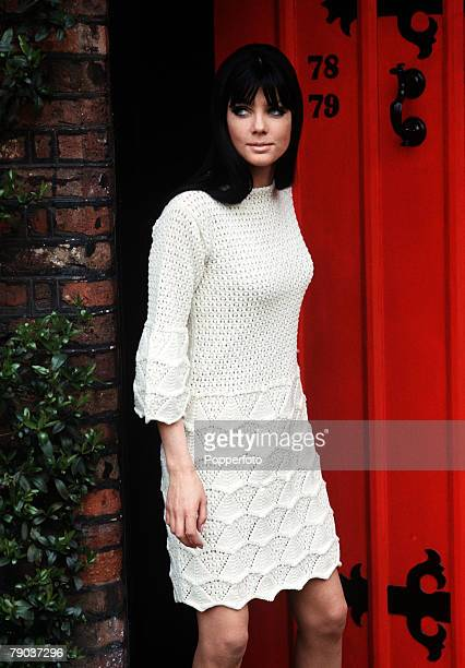 Fashion 1960s Knitwear A young woman with dark hair and piercing blue eyes steps away from a red door while wearing an intricately knitted cream...
