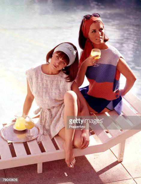Fashion 1960s Knitwear Two young women sit on a sun lounger together drinking fruit juice near the waterside Each of them wears a tabard style...