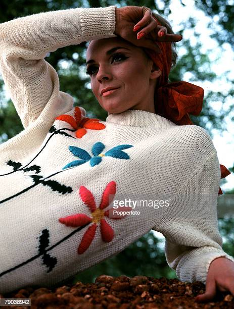 Fashion 1966 Knitwear A model with fashionably heavy make up and a headscarf sits under trees wearing a knitted sweater with applique embroidered...