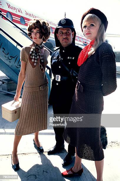 Two glamorous smartly dressed women and a Jordanian policeman stand outside in front of an aeroplane The women are holding hand luggage