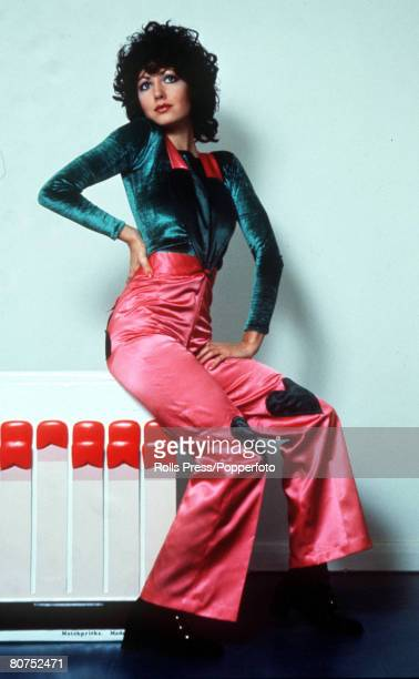 Fashion 1971, A woman wearing bright pink satin flares and green top