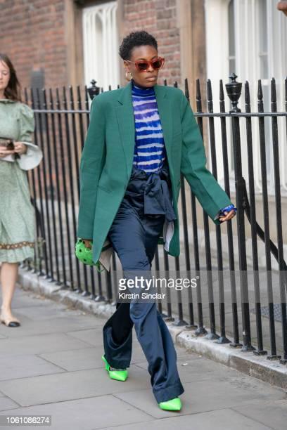 Fashion and Accessories editor at British Vogue Donna Wallace wears Rejina Pyo sunglasses, Joseph blazer, navy silk trousers and green stilettos...