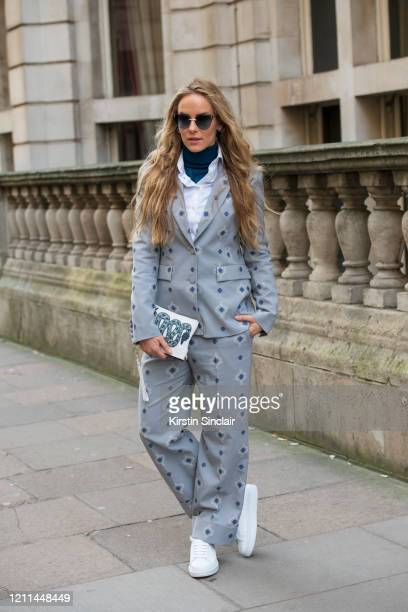 Fashion and lifestyle Pr Hum Fleming wears a Daks suit and trainers blue sunglasses and a white clutch bag with a blue embroidered snake on during...