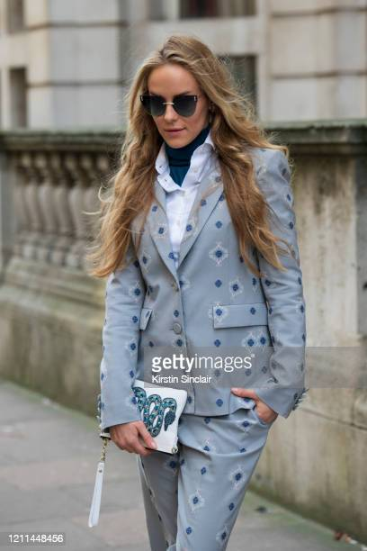 Fashion and lifestyle Pr Hum Fleming wears a Daks suit blue sunglasses and a white clutch bag with a blue embroidered snake on during London Fashion...