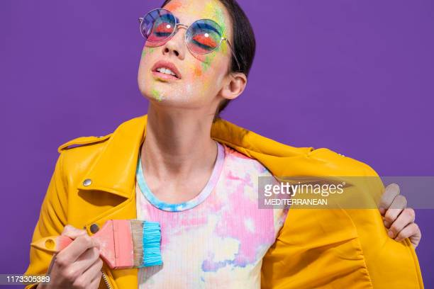 fashion artist painter girl with brush painting herself t-shirt on purple - purple coat stock pictures, royalty-free photos & images