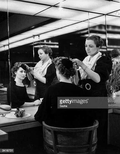 A fashion assistant ftting a hat to a customer at Harrods department store in London