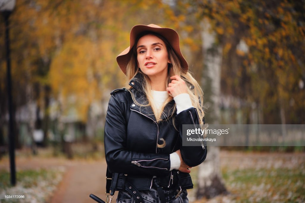 fashion autumn portrait of young happy woman walking outdoor in fall park in hat and leather jacket : Stock Photo