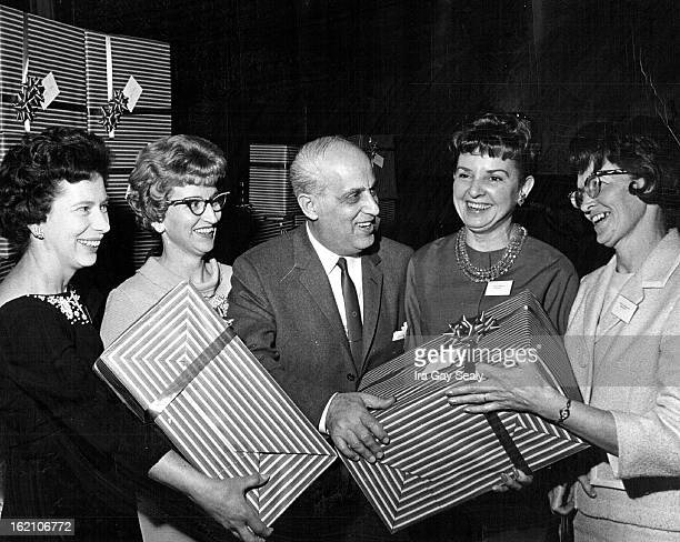 FEB 22 1965 Fashion Bar Honors Salesgirls George Vince center controller for the Fashion Bar stores in Denver presents gifts to top salesgirls at a...