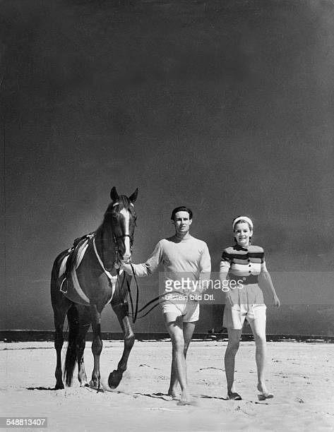 Fashion - beach fashion: Young couple with horse on the beach, the man wearing white linen shorts with a high-necked sweater by Steinhardt and the...