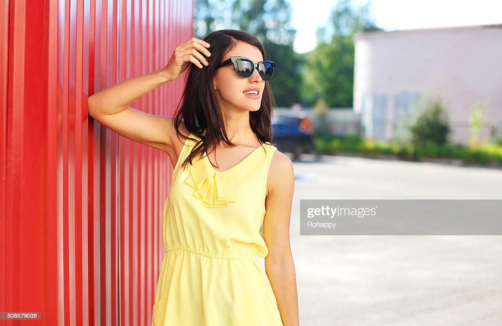 Fashion beautiful woman wearing yellow dress and sunglasses in city : Bildbanksbilder