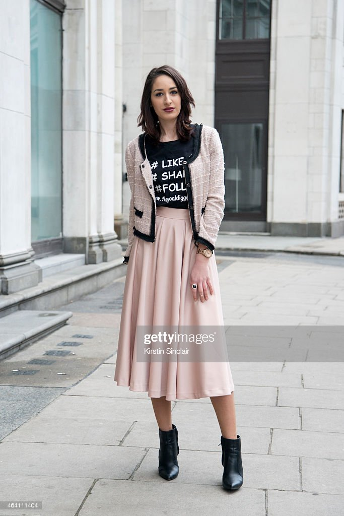 Fashion blogger Adela Ionescu wears a Zara jacket, H and M skirt, New Look shoes and her own design t shirt on February 21, 2015 in London, England.
