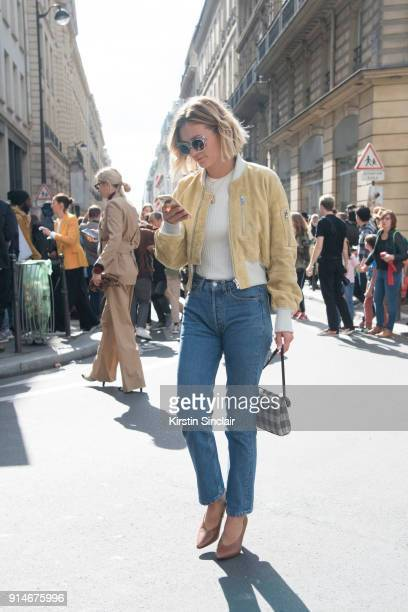 Fashion blogger Adenorah AnneLaure Mais wears an Acne jacket top and shoes Levi'u2019s jeans Mansur Gavriel bag and vintage sunglasses day 5 of Paris...