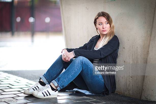 Fashion blogger Amelie Lloyd wearing Sandro jeans and belt an Asos top a Zara trench and Adidas shoes during a street style session on February 14...