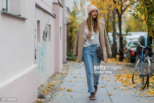 Fashion Blogger and Owner of SCIC Swimwear Sofia Grau holding a coffee to go wearing light blue two tone HM denim jeans a pink wool hat other stories...
