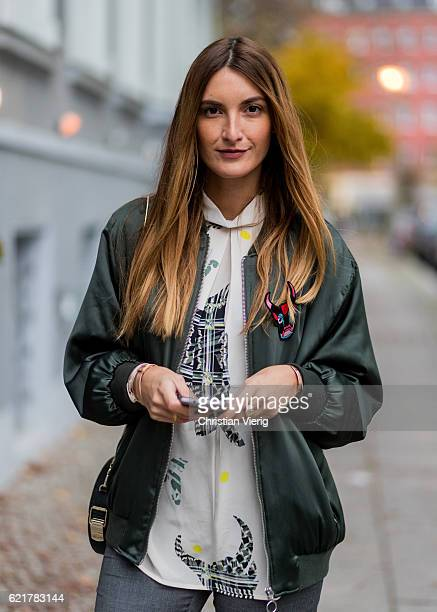 Fashion Blogger and Owner of SCIC Swimwear Sofia Grau on her phone wearing a white blouse Lala Berlin a green jacket Zara grey ruffled pants...