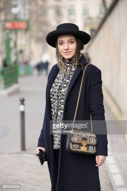 Fashion blogger Andreea Cristea of stilettoshades wears a Dior bag and hat Coat Co coat and a Chanel jacket day 2 of Paris Womens Fashion Week...
