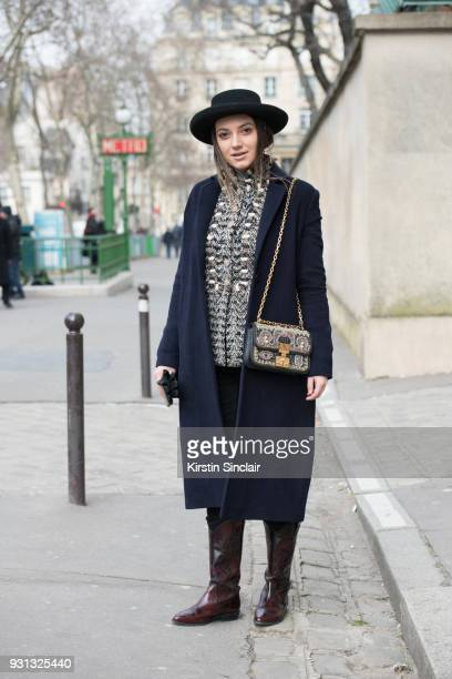 Fashion blogger Andreea Cristea of stilettoshades wears a Dior bag and hat River Island boots Coat Co coat and a Chanel jacket day 2 of Paris Womens...