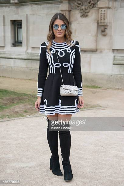 Fashion blogger Ariane Canovas wears a Bambola dress Chanel bag Schutz boots and Ray Ban sunglasses on day 8 of Paris Collections Women on March 10...
