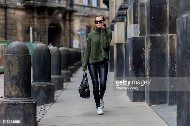 Fashion Blogger Barbora Ondrackova is wearing an olive green Asos sweater black Balenciaga leggings a black Yves Saint Laurent bag white Converse...
