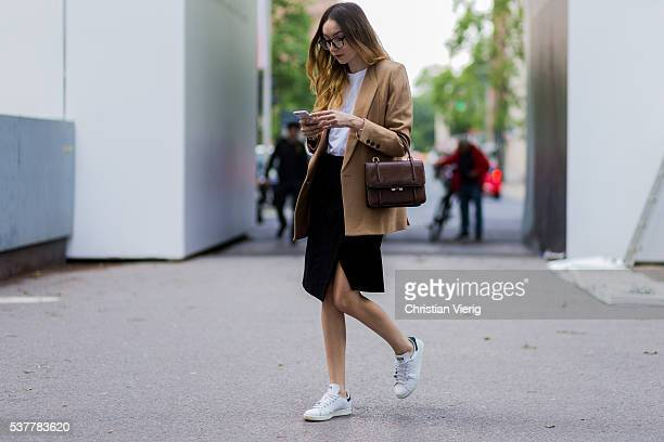 Fashion blogger Beatrice Gutu wearing glasses a beige Frontrowshop blazer white Asos tshirt a black Edited skirt vintage bag and white Adidas Stan...