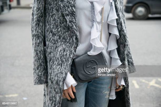 Fashion blogger Camila Carril wears a Haizhen Wang coat Levi's jeans Sister Jane shirt and Gucci bag on day 5 of London Womens Fashion Week...