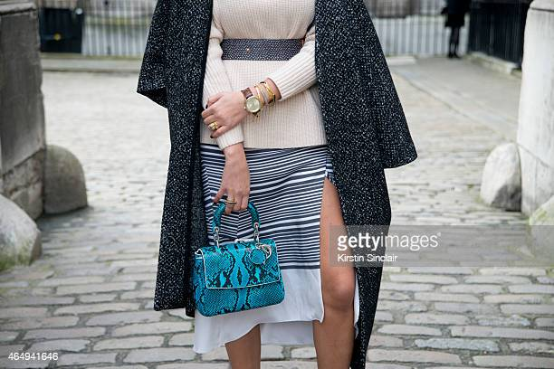 Fashion blogger Camila Carril wears a Smart and Ginger dress and belt French Connection coat Dior bag Reiss top on February 24 2015 in London England