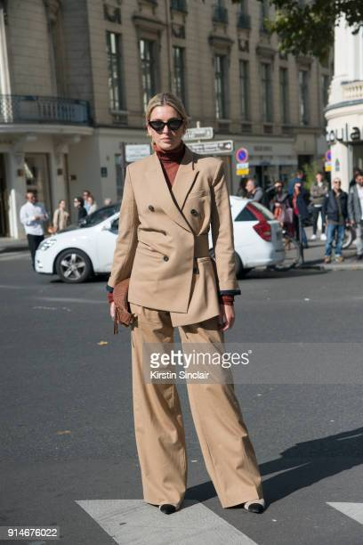 Fashion blogger Camille Charriere wears an Acne polo neck sweater Victoria Beckham suit Nanushka bag Chanel boots and Le Specs sunglasses day 5 of...