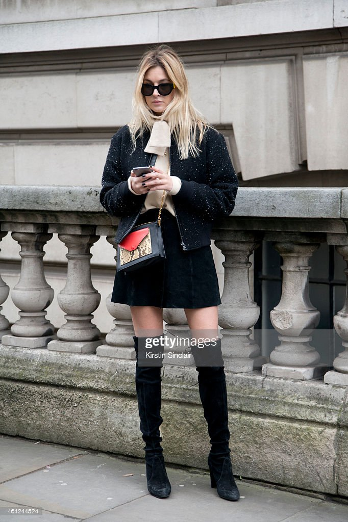 Fashion Blogger Camille Charriere wears Stuart Weitzman boots, Rag and Bone jacket, Christoph Lemer top and Celine bag and sunglasses on day 3 of London Collections: Women on February 22, 2015 in London, England.