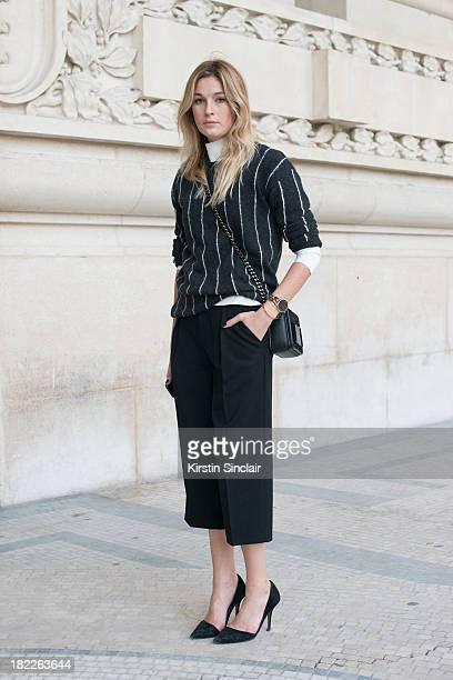 Fashion Blogger Camille Charriere wears Zara top and shoes Club Monaco trousers H and M bag and Mango knitwear on day 5 of Paris Fashion Week...