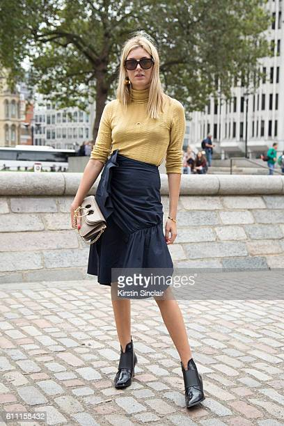 Fashion blogger Camille Sheria wears JW Anderson skirt and bag Creatures Of The Wind top Celine sunglasses and Jimmy Choo shoes on day 3 of London...