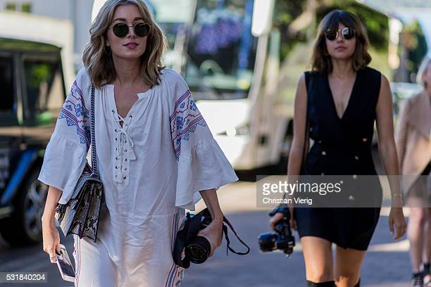 Fashion blogger Carmen Hamilton wearing a white tunic dress and a Gucci bag and Talisa Sutton wearing a sleeveless dress with golden buttons with...