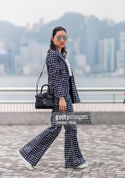Fashion Blogger Carol CharlotteBlair wearing sunglasses a navy Max Mara suit with star print a white cropped tshirt a black Delvaux bag white Miu Miu...