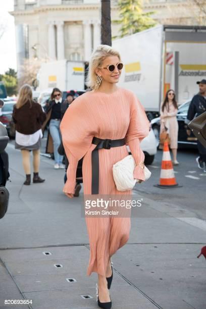 Fashion blogger Caroline Daur wears Dior shoes Jil Sander dress Loewe bracelet Miu Miu bag on day 3 during Paris Fashion Week Autumn/Winter 2017/18...