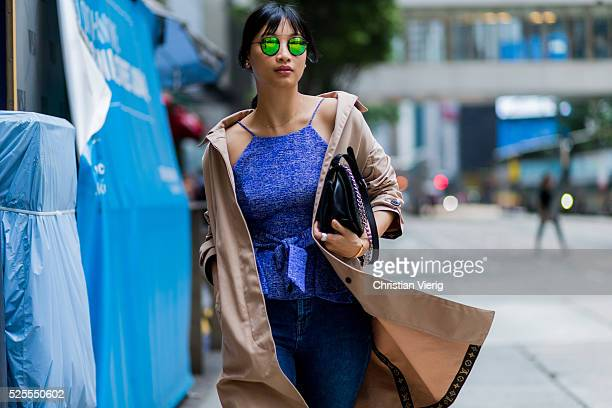 Fashion blogger Cindy Ko wearing Spektre round sunglasses a black Dior bag a beige Louis Vuitton trench coat a blue Lane Crawford x Cmeo Collective...