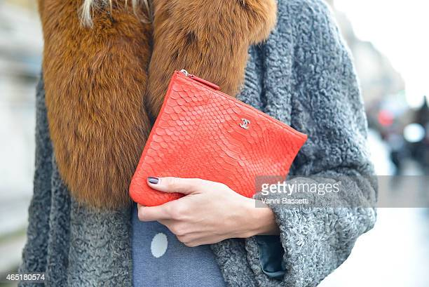 Fashion blogger Elizabeth Minett poses wearing a vintage coat Asilio top and Chanel clutch on March 3 2015 in Paris France