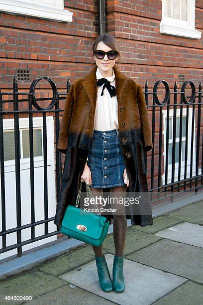 Fashion blogger Ella Catliff wears a Burberry coat Mulberry bag and boots Maje shirt Alexa Chung for AG Jeans and Kirk Originals sunglasses on...