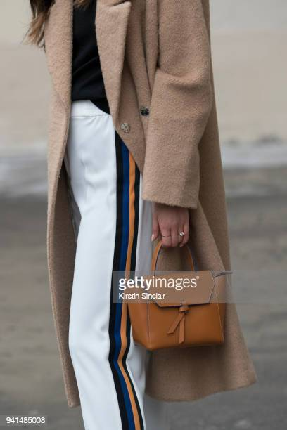 Fashion blogger Felicia Evalina wears Zara trousers Day Birger et Mikkelsen coat and an Alexandra de Curtis bag day 4 of Paris Womens Fashion Week...