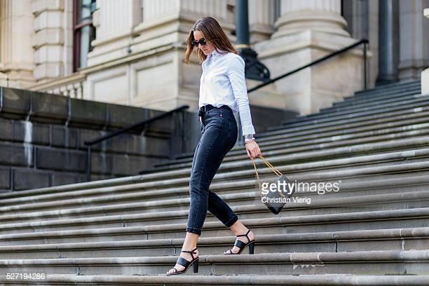 Fashion blogger Holly Titheridge wearing black sunglasses a white Topshop button shirt black Topshop denim jeans black Alias Mae heel sandals black...