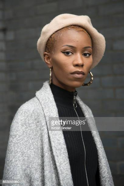 Fashion blogger Irene Iredia wears a Miss guided dress and jacket Urban Outfitters hat and earrings on day 1 of London Womens Fashion Week...