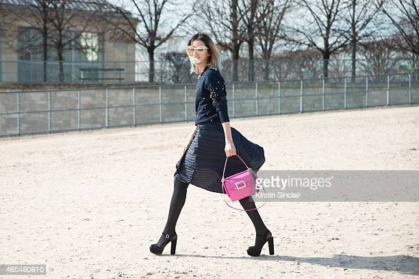 Fashion blogger Irene Kim wears an Issey Miyake skirt Roger Vivier bag a Chanel top Gentle Monster sunglasses Prada shoes and a Chanel cuff on day 4...