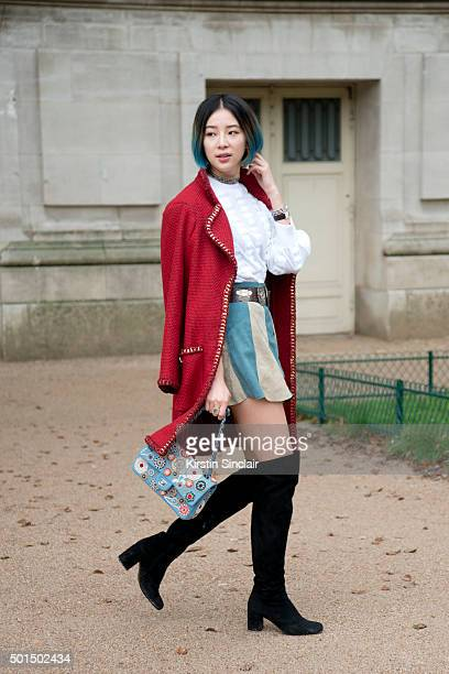 Fashion Blogger Irene Kim wears Saint Laurent boots vintage skirt and belt and a Chanel jacket bag and top on day 8 during Paris Fashion Week...