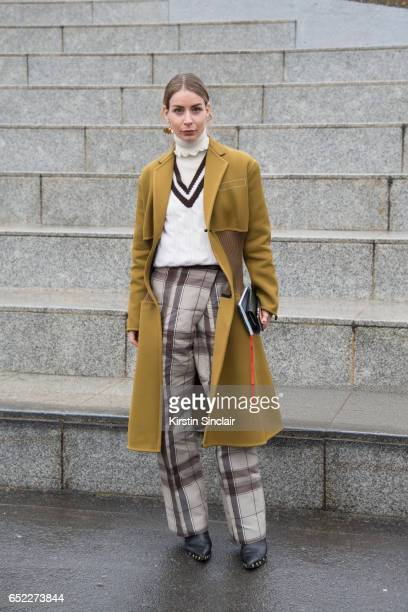 Fashion blogger Irina Lacikevic wears a Trademark turtle neck sweater Celine boots coat and trousers and a Christopher Kane sweater on day 2 during...