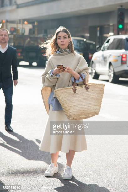 Fashion blogger Irina Lakicevic wears a Celine sweater and skirt Adidas trainers and a vintage bag on day 4 of London Womens Fashion Week...