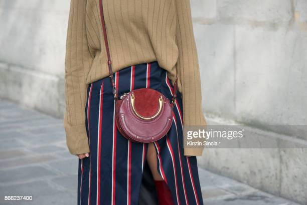 Fashion blogger Julia Haghjoo wears a Samsoe Samsoe sweater, Solace London skirt, Chloé bag day 2 of Paris Womens Fashion Week Spring/Summer 2018, on...